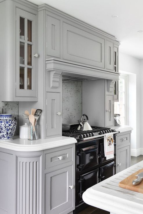 Fabulous kitchen boasts gray cabinets painted Zoffany Paint Silver accented with round silver pulls alongside sleek white counters and an antiqued mirrored backsplash. The kitchen features a black Aga Range under a gray kitchen hood with shelf flanked by gray pull out spice cabinets framed by glass front upper cabinets and curved end cabinets.