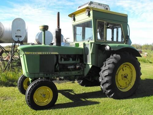 Old John Deere tractors.Looks like a John Deere 3020 or 4020 standard tractor
