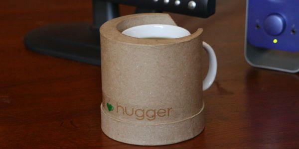 Mug Hugger. Keep your beverage warm with a Mug Hugger. The outer shell of the Mug Hugger is made of a biodegradable coated paper. The inside consists of a patented material that retains heat when microwaved. The 5″ diameter base will stop spillage.