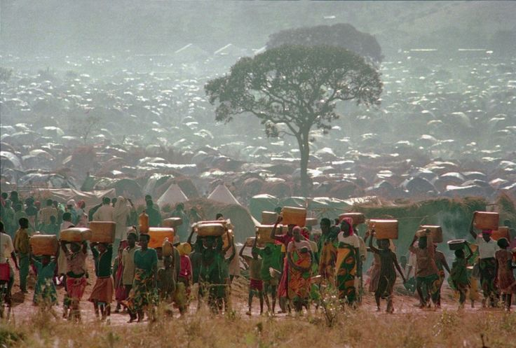 Rwanda: Refugees carrying water containers make their way back to huts at the Benaco Refugee Camp in Tanzania in 1994. At the time the camp had a population surpassing 300,000, making it the largest refugee settlement in the world. Aid agencies had difficulty feeding, doctoring and sheltering the refugees who fled the ethnic bloodbath in neighboring Rwanda. (Karsten Thielker/AP)