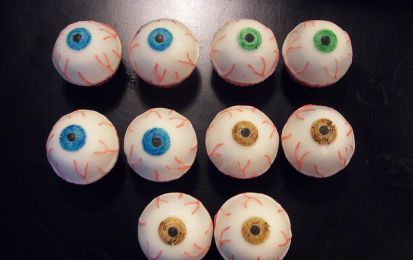 Occhi insanguinati di Halloween - La ricetta di Halloween con occhi insanguinati è semplice e veloce: praline di biscotti secchi e ricotta ricoperti di cioccolato bianco e decorati con bottoni di cioccolato bianco spaventeranno e divertiranno i vostri ospiti.