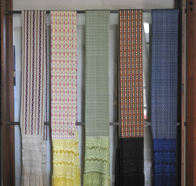 Rebozos Mexico    Display of handwoven (backstrap loom) rebozos at the rebozo weaving school in Santa Maria del Rio, San Luis Potosi state, Mexico. The gray rebozo at far left is woven from pure silk. The other 4 rebozos are woven from artisela (artificial silk -- a synthetic fiber). The silk rebozo cost 3 times as much as the artisela rebozos.