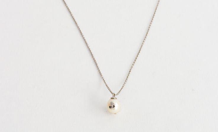 Cadena de plata con incrustación en plata con forma de corazón sobre perla blanca.
