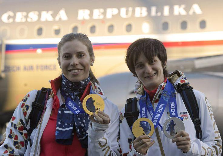 Olympijské vítězky Eva Samková (vlevo) a Martina Sáblíková pózují  s medailemi po příletu první části české výpravy na letiště Praha-Kbely.