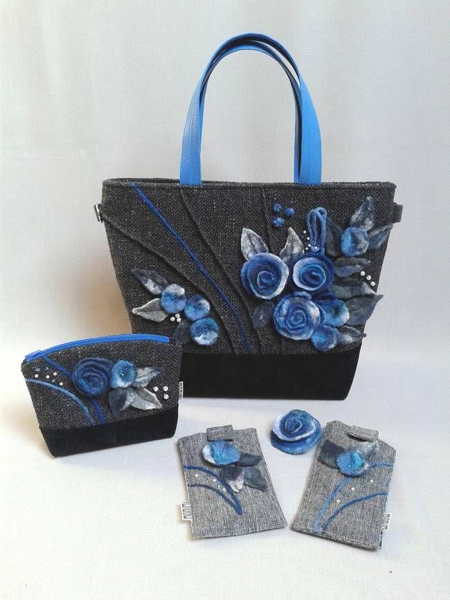 """A Monimi Exclusive táskákból csak egyetlen darab készül. Teljesen egyedi és ezáltal te is az lehetsz! Ez a szürke táska mégsem """"szürke"""", hanem kitűnik a tömegből! Feltűnő, mégis elegáns. Gyönyörű a kék minden árnyalatát felvonultató rózsákat, virágokat, bogyókat nemezeltem rá, amiket szürke levelekkel, gyöngyökkel egészítettem ki.  A díszítés érdekessége a raffolás, amely több helyen végig fut a táska elején, ezzel mozgalmassá téve a felületet. #exclusive #női #táska"""