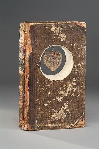 The clean edges of the cut paper really contrasts with the shabby exterior of this old book. I wonder what the title is.