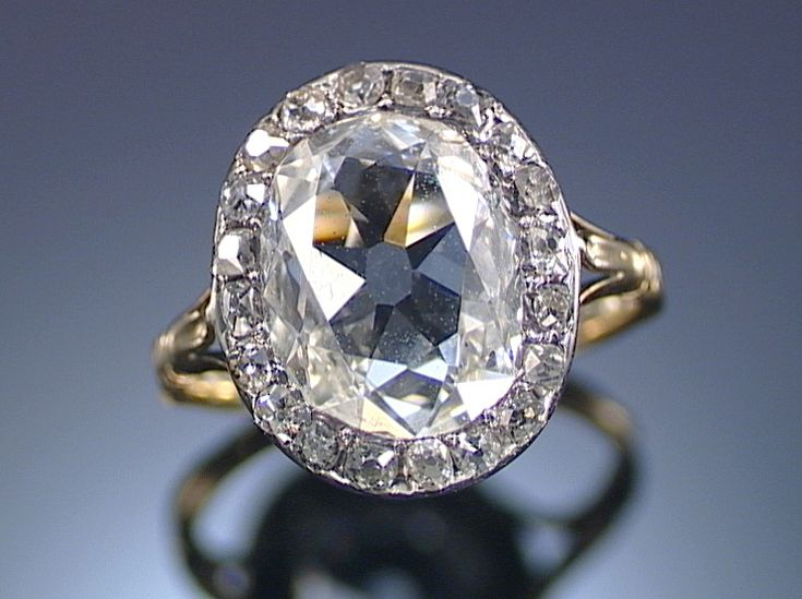 DIAMOND RING, EARLY 19TH CENTURY.  Centering on an oval diamond within surrounds of single-cut stones