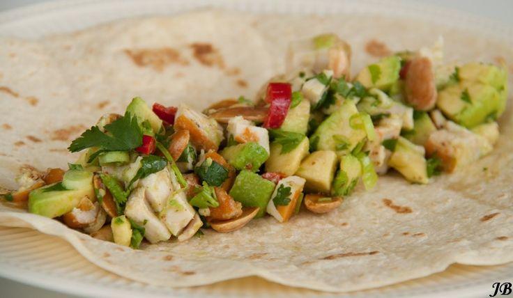Ingrediënten:  - 4 grote tortilla wraps - 1 gerookte kipfilet, in blokjes gesneden - 2 rijpe avocado's, in blokjes gesneden - 1 rood pepertj...