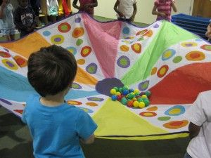 Van alleen de kleuren word je al blij. De spelletjes ontstaan met de parachute vanzelf.