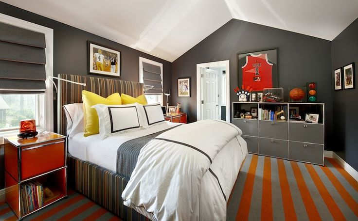 charcoal gray walls and a white vaulted ceiling. a gray, orange and white striped bed dressed with a gray coverlet, white sheets, yellow euro shams with black hotel pillow shams and duvet cover. The bed is flanked by a pair of modern orange nightstands with chrome trim. A framed sports photograph hangs over the headboard.  gray roman shades. a gray locker style cabinet holds an array of sports memorabilia. A framed sports jersey hangs over the locker.