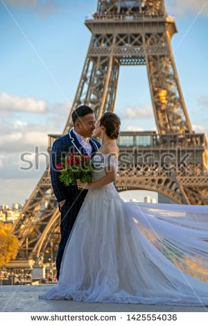 Stock Photo: Paris, France – November 13, 2018: Newly married asian couple posin…