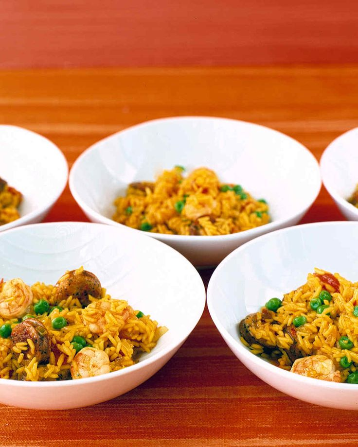 Easy Paella | Martha Stewart Living - This easy version of the Spanish favorite combines chicken, sausage, and shrimp with long-grain rice, peas, and canned tomatoes. Saffron, which usually gives paella its brilliant yellow-orange hue, is replaced here by budget-friendly turmeric.