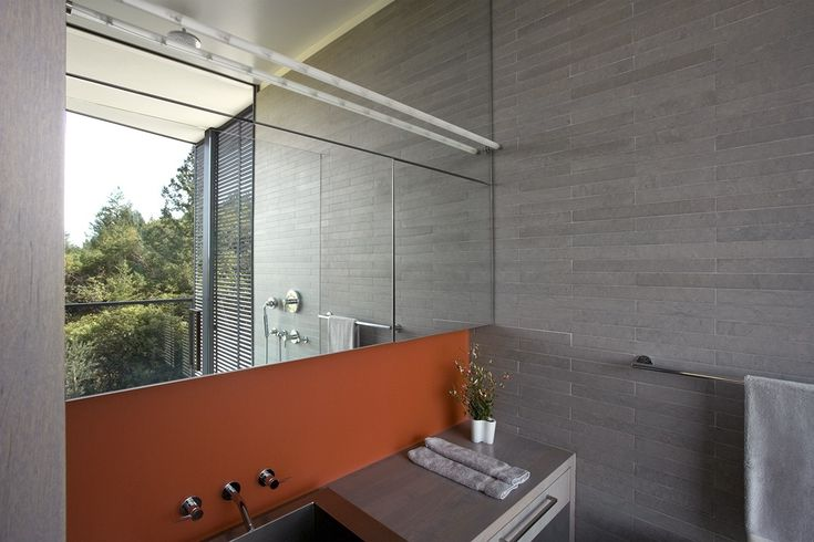 French Blue limestone tile lines the walls of the bathroom, where the shower's glass window takes in views. The orange backsplash, made of 3 Form Chroma, provides a pop of color alongside the Julien sink and Dornbracht fixtures.