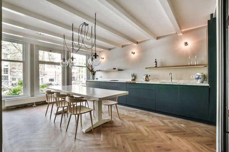Deze greeploze antraciete keuken is voorzien van een marmeren werkblad. Het strakke design is verfraaid met houten wandplankjes en sfeervolle wandlampjes. In combinatie met het houten balken plafond en de visgraatvloer is het een mooie mix tussen modern en klassiek. Ontwerp BNLA architecten. Keuken Eginstill.