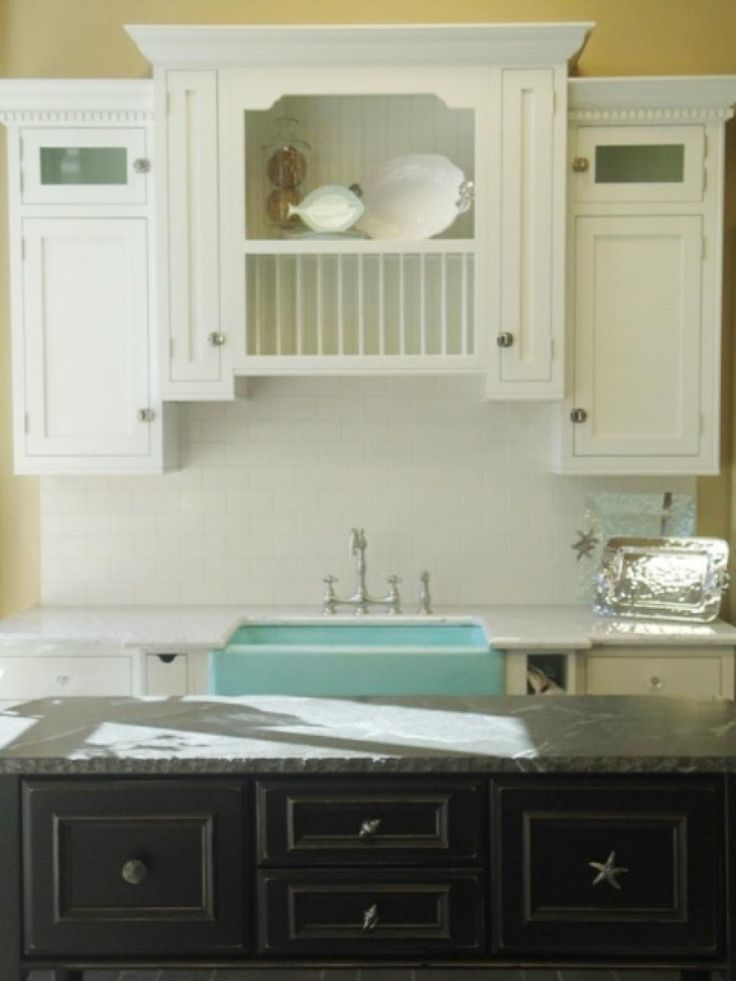Designer Anissa Swanzy paired white cabinets with a green farmhouse sink for a clean, crisp look that personifies ocean waves. White subway tiles and Carrera marble enhance the clean look, which is offset by a black kitchen island.