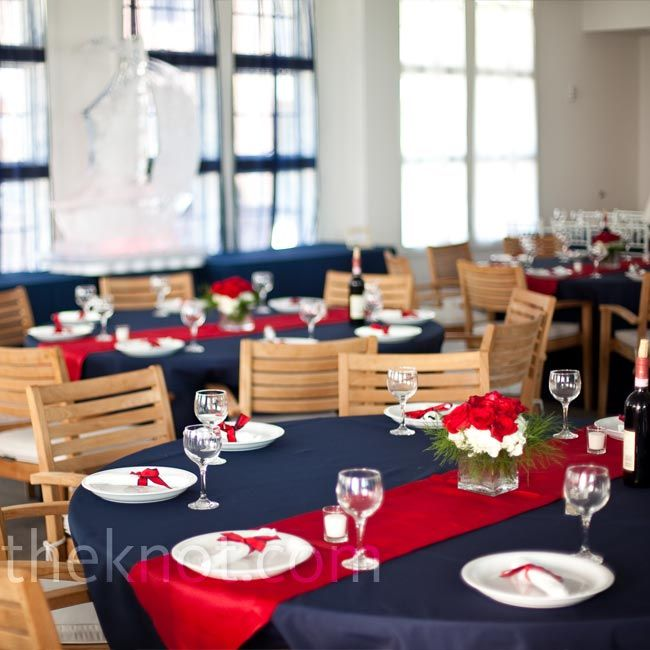 On the reception tables, bright red table runners laid atop classic navy linens. To complement the nautical décor, the couple used red and w...