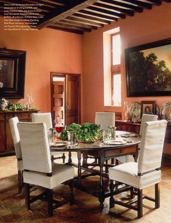 Dining with muted orange walls, ceiling beams, round table - Axel Vervoordt