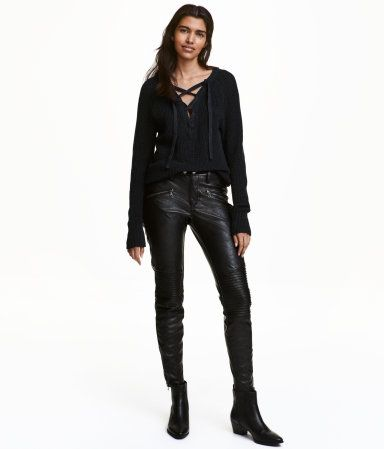 Black. Low-rise biker pants in stretch imitation leather. Zip fly with button, mock front pockets with decorative zips, regular back pockets, quilted