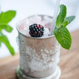 "We came across this recipe while, uh, ""working."" Sloe gin, crème de cassis, and fresh blackberries present a fruity profile without sweetening the classic Mint Julep up too much, making this one of our favorite variations."