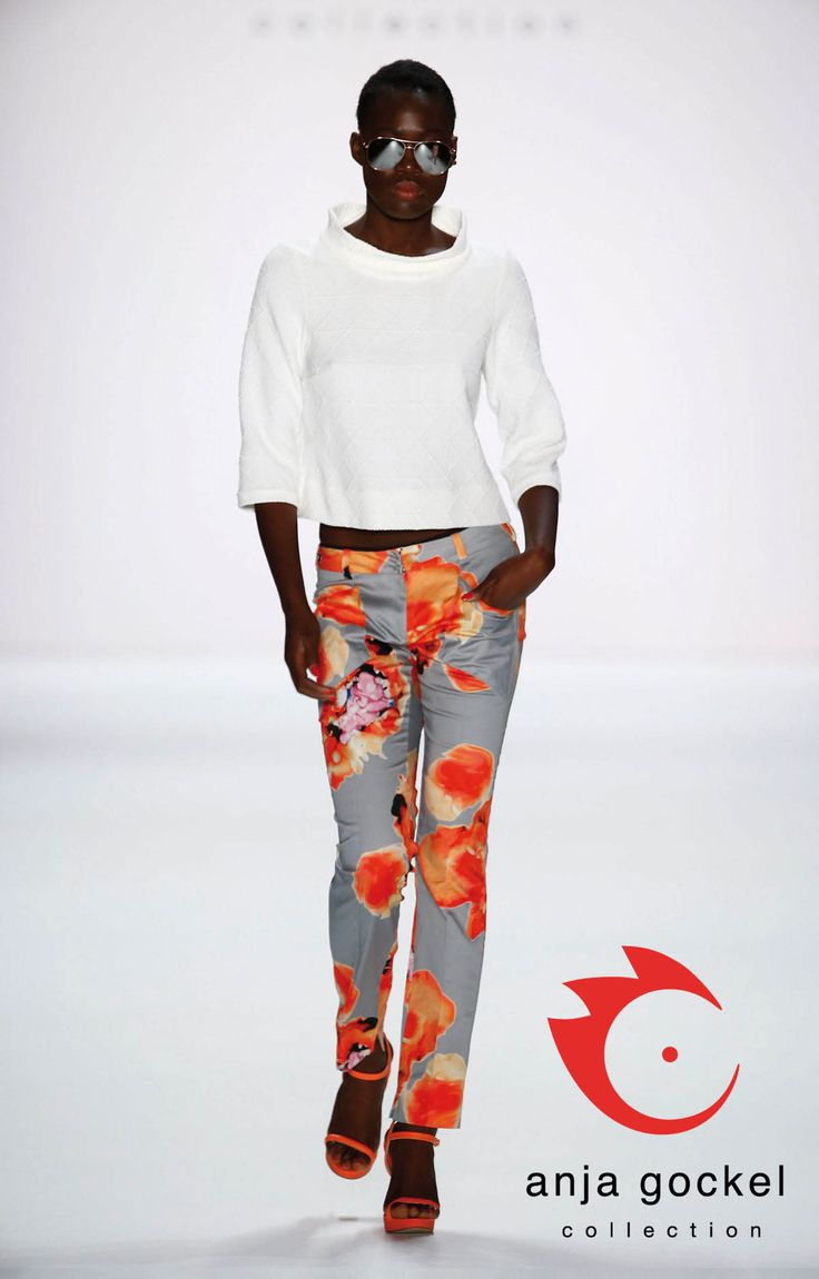 Model Aminata Sanogo for anja gockel, wearing a pure white, structured sweater with an oversized stand-up collar teamed with a straight cut diva trousers in anja gockels blurred poppy-print on a grey background.