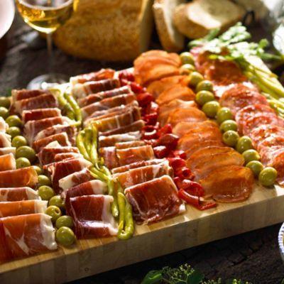 Buffet de embutidos variados. Bonita manera de presentarlos. Con olivas y pepinillos en una tabla de madera. Se puede hacer en una tabla más pequeña, según convenga.