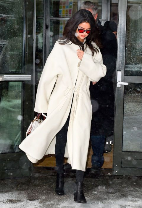 Selena Gomez went winter white wearing The Row and Coach while out in New York City. She topped off her effortless look with black boots and her fave red lens sunglasses.