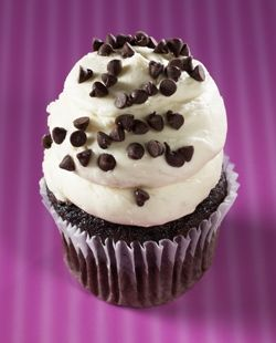 Gigi's Cupcakes - White Midnight Magic: Dark chocolate cake with dark chocolate chips, topped with a white cream cheese frosting and chocolate chips.