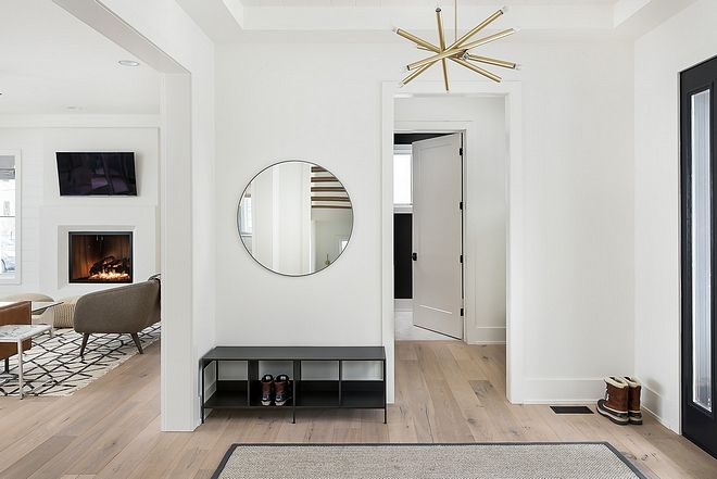 The Foyer Features White Oak Hardwood Floors White Walls Modern Brass Chandelier And A Round Mirror Minimalist Entryway Discount Bedroom Furniture Home