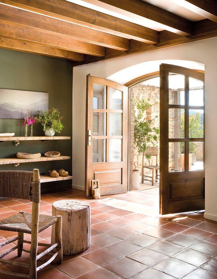 Recibidor de casa rústica con puertas en arco y baldas en la pared. Recibidor rústico-actual con baldas de madera y pared pintada en verde oliva
