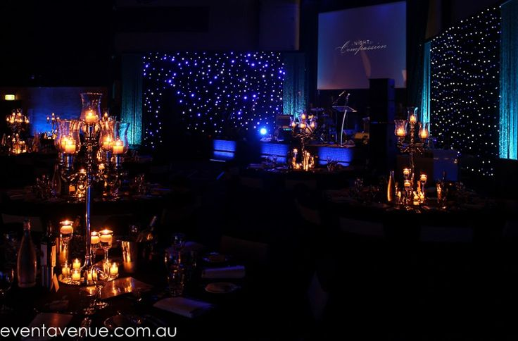 Elegant wedding reception with stunning candle holder with lighted candles and sparkling center stage with band complimenting the night event.