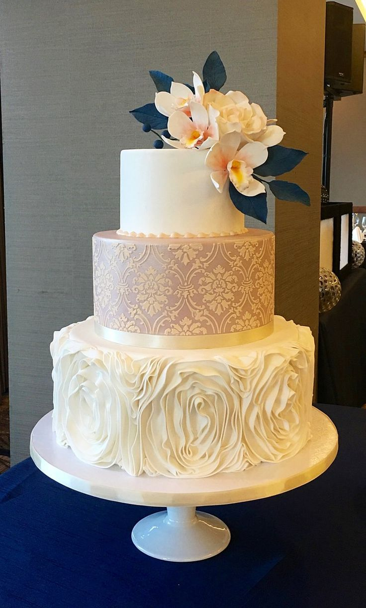 Dusky pink and navy damask cake with ruffle rosettes and sugar flowers. Image copyright Carla Schier.