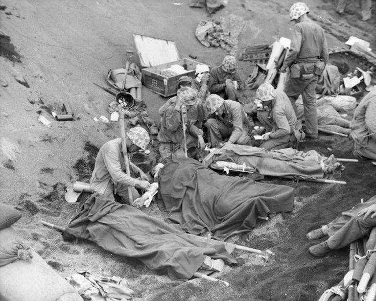La marine américaine médecins et hommes du corps de santé traitent les blessés Marines américains à un poste de secours mis en place dans un ravin sur Iwo Jima, dans le Pacifique, le Japon, le 6 mars 1945. Le plasma sanguin et le sang total est administré des approvisionnements de la côte ouest des États-Unis.