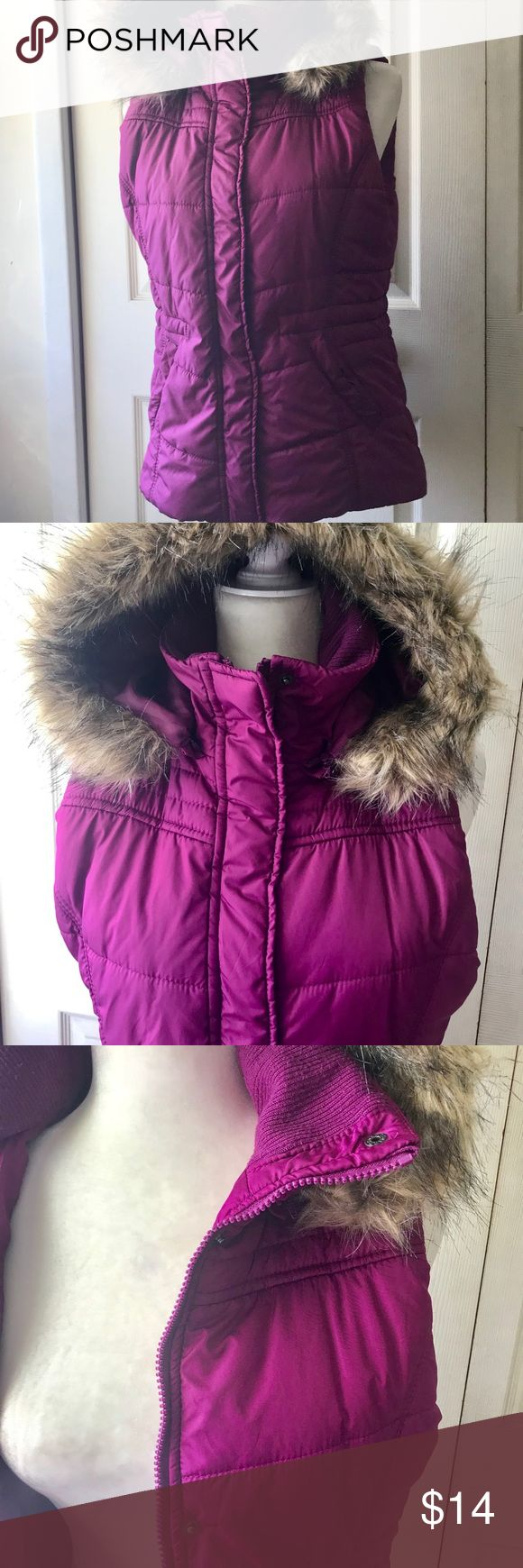 "Ladies Polyester vest with removable hood Pre owned excellent condition 100% polyester machine washable vest with faux fur removable zip off hood. 2 pockets in front 1 slip pocket with snap closure, adjustable elastic pulls at waist.  Length from back neck is 25"" underarm to underarm 21"" laying flat. Front zipper and snap closures. Color is deep pink/magenta New York & Company Jackets & Coats Vests"
