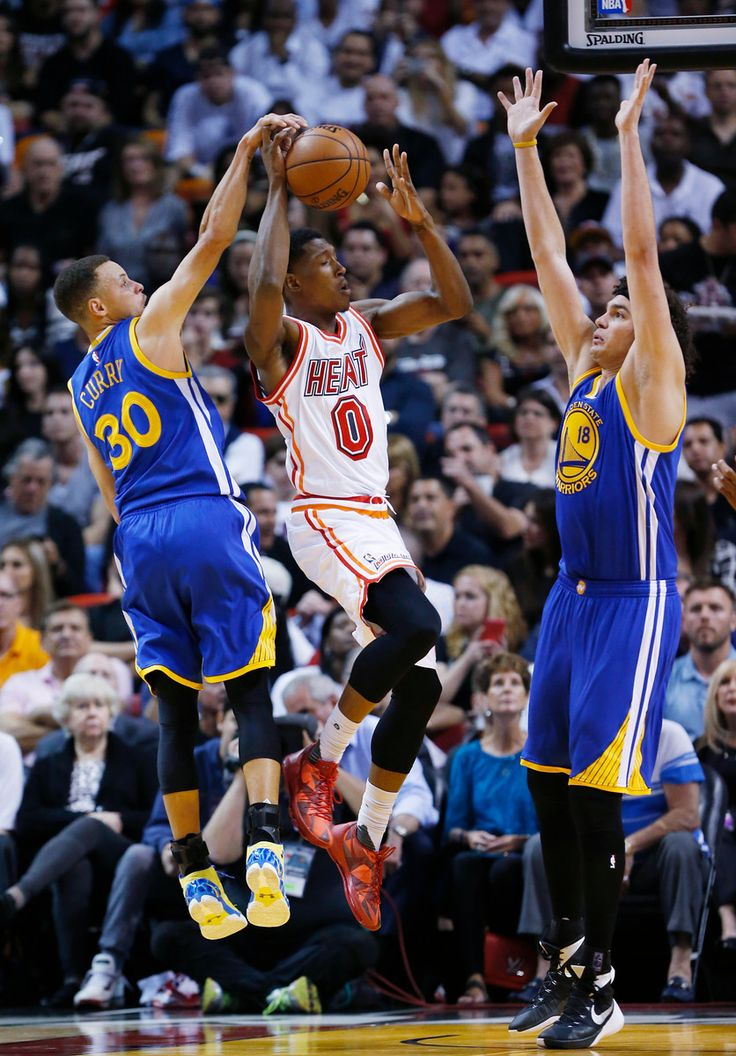 . Miami Heat guard Josh Richardson (0) goes up for a shot against Golden State Warriors guard Stephen Curry (30) and center Anderson Varejao (18) during the first half of an NBA basketball game Wednesday, Feb. 24, 2016, in Miami. (AP Photo/Wilfredo Lee)