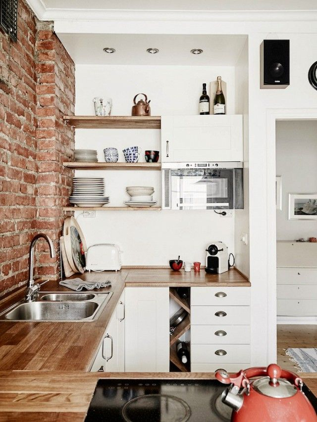 This tiny Swedish kitchen has something many Scandinavian spaces don't: warmth. We love how its designers extended the earthy tones of the brick wall into the shelving, cabinetry, and teapots!