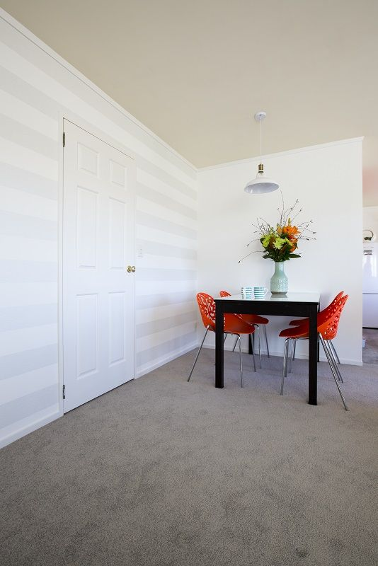 The final reveal! Subtle silver striped wallpaper hung horizontally, teams up with soft greige coloured carpet and a splash of orange in the accessories. Decorating products are available in New Zealand through Guthrie Bowron stores.