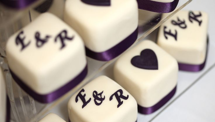 Our wedding cake... mini sponge cakes with purple lettering and ribbon