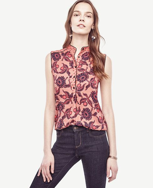 """Contrast piping adds modern definition to this crisp crepe essential. Mandarin collar. Sleeveless. Button front placket with pleat beneath. Forward shoulder seams. Back yoke with inverted pleat and side pleats. Shirttail hem. 27"""" long."""