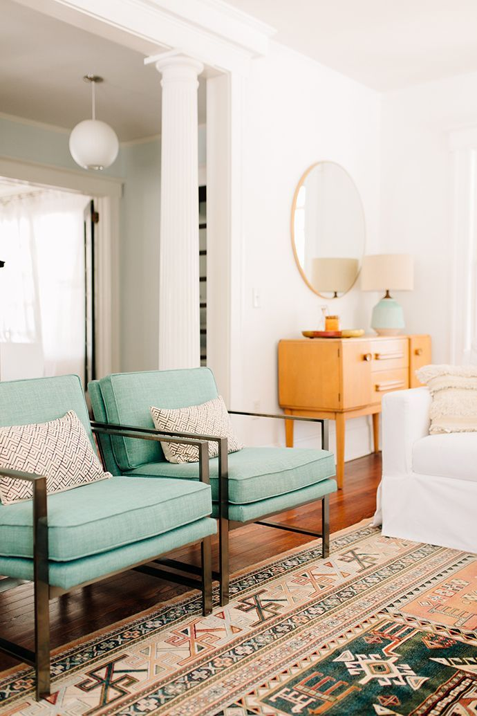 Mid century modern living room with pale aqua upholstered mid century chairs and vintage rug