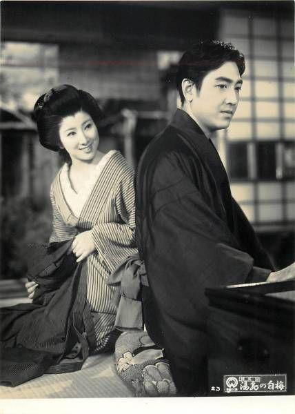 縦縞の着物を着て男性に微笑みかける若い頃の山本富士子