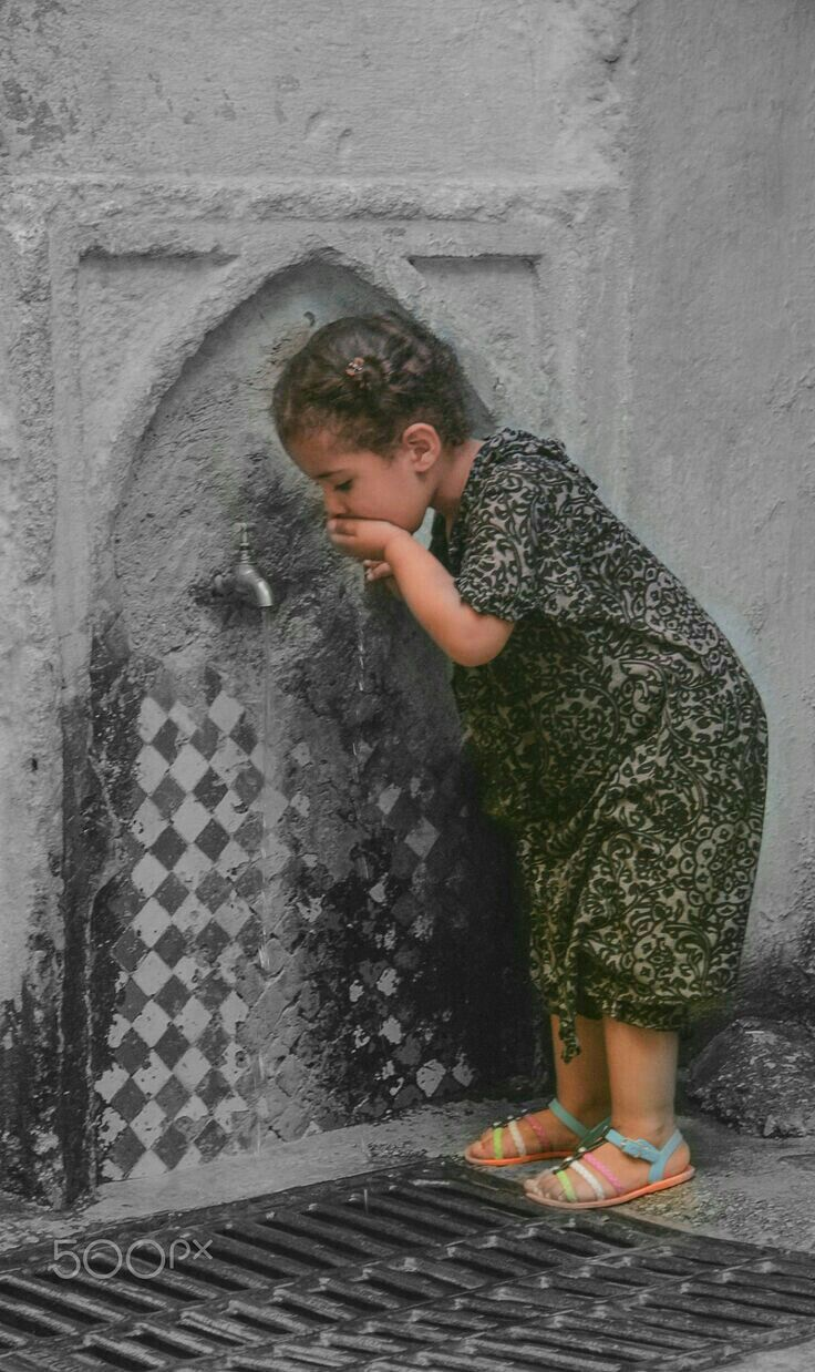 A little girl drinking water from a fountain in Fez