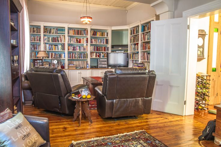 This lounge has a fireplace and a built-in cabinet too. Like the many other rooms of this house this room is capacious and cosy.