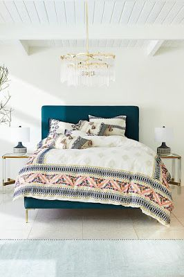 white room, aquamarine headboard, patterned bedsheets, plain rug, chandelier over bed