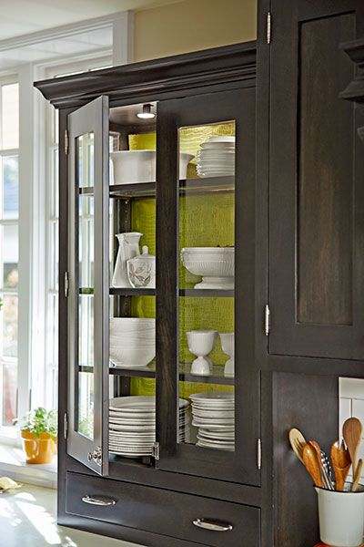 Glass shelf inserts allow lights to brighten the entire contents of this black china cabinet. The back is lined with wrapping paper in the perfect shade of chartreuse green.
