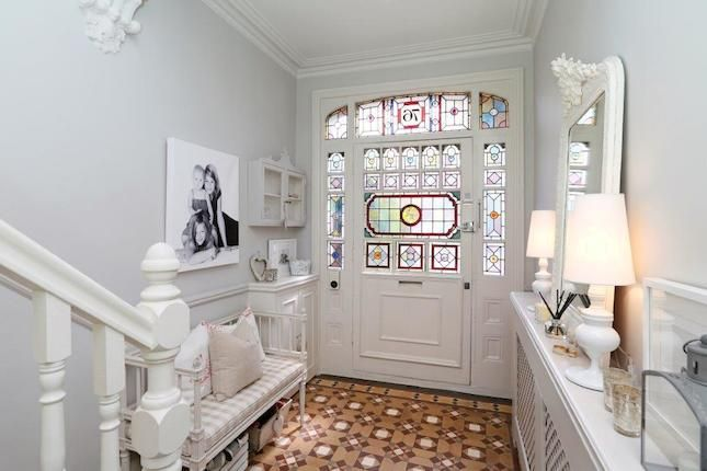 Beautiful stained glass in the door.  Very plain white hallway and door goes well with it
