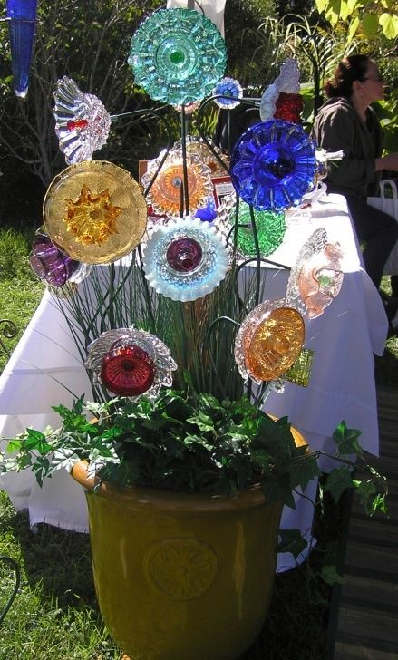 Thrift store glass plates into garden flowers.