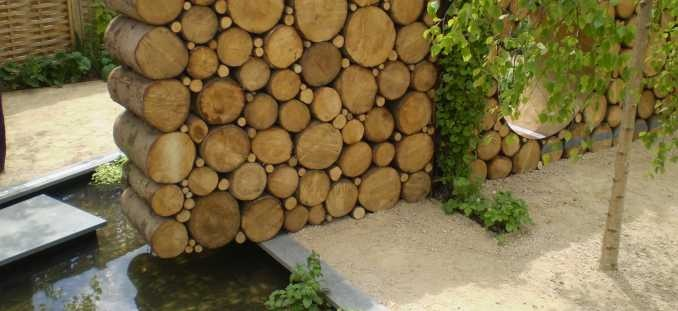 Log wallmade from cut up trees stacked up smaller branches put in between holes  Recycled