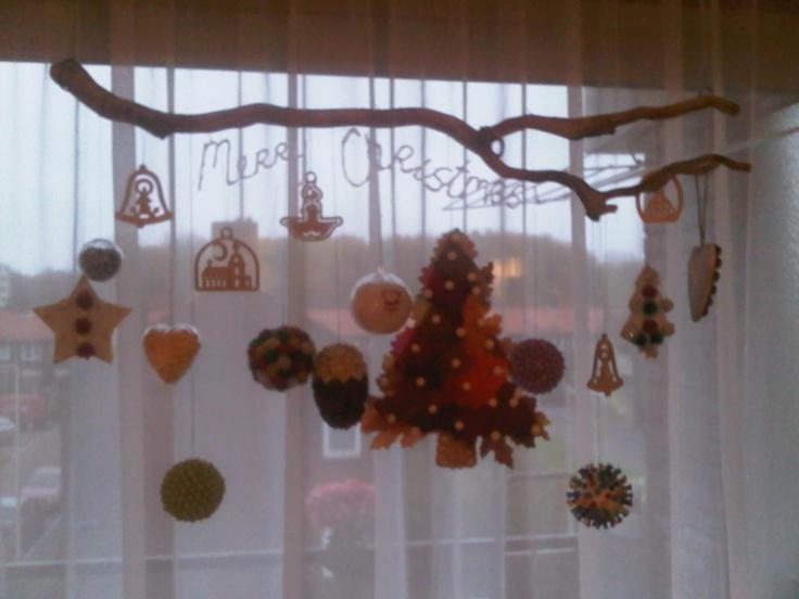 leuke kerst versieringen zelf maken en deze ophangen voor het raam.