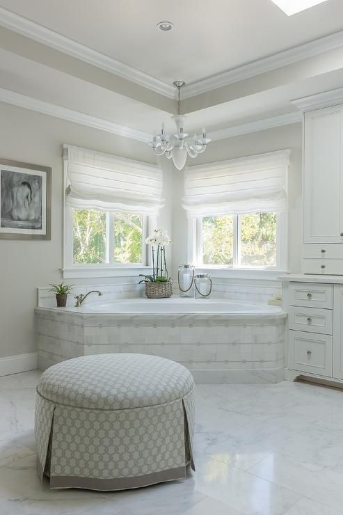 Beautiful master bathroom boasts a corner marble tiled tub placed under windows dressed in white roman shade illuminated by a white chandelier alongside a round skirted ottoman with grey ribbon trim.
