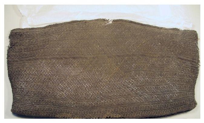 Black finely woven kete, or Maori basket. Large black elaborately patterned kit, said to be of kiekie and used for soaking karaka berries in water.